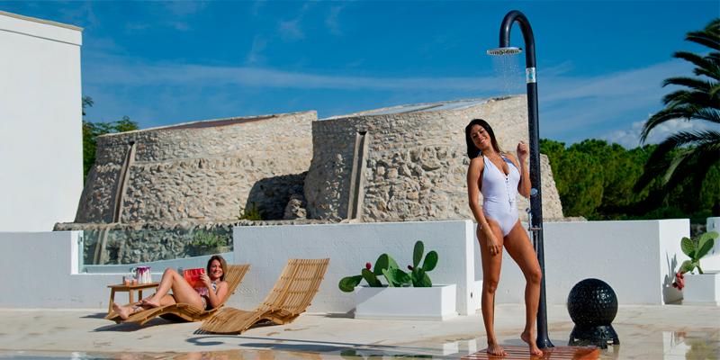 mujeres junto a la piscina con una ducha solar en resina negra